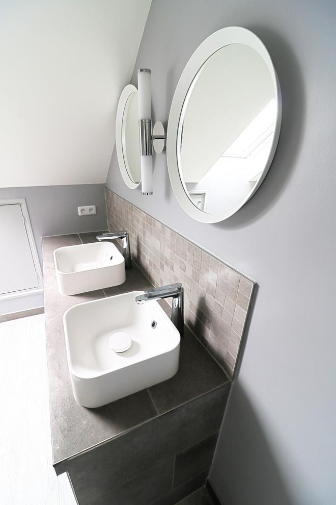 Cette photo montre une grande salle de bain principale tendance avec un placard à porte affleurante, des portes de placard grises, une douche à l'italienne, un carrelage gris, des carreaux de céramique, un mur gris, un sol en bois peint, un lavabo posé, un plan de toilette en carrelage, un sol gris et un plan de toilette gris.