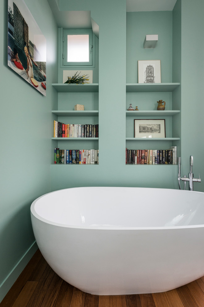 Freestanding bathtub - small contemporary master medium tone wood floor freestanding bathtub idea in Paris with open cabinets and green walls