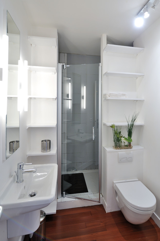 Inspiration for a small contemporary 3/4 dark wood floor alcove shower remodel in Paris with a wall-mount sink, a wall-mount toilet, white walls, open cabinets and white cabinets