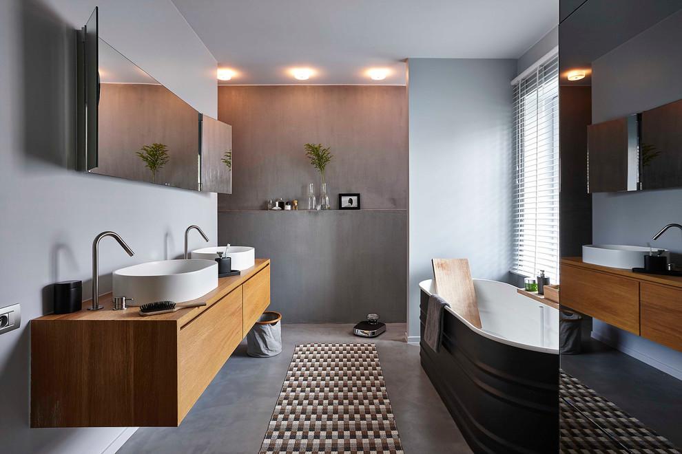 Inspiration pour une salle de bain principale design de taille moyenne avec un placard à porte plane, des portes de placard en bois brun, une baignoire indépendante, un mur gris, béton au sol, une vasque, un carrelage gris et un plan de toilette en bois.