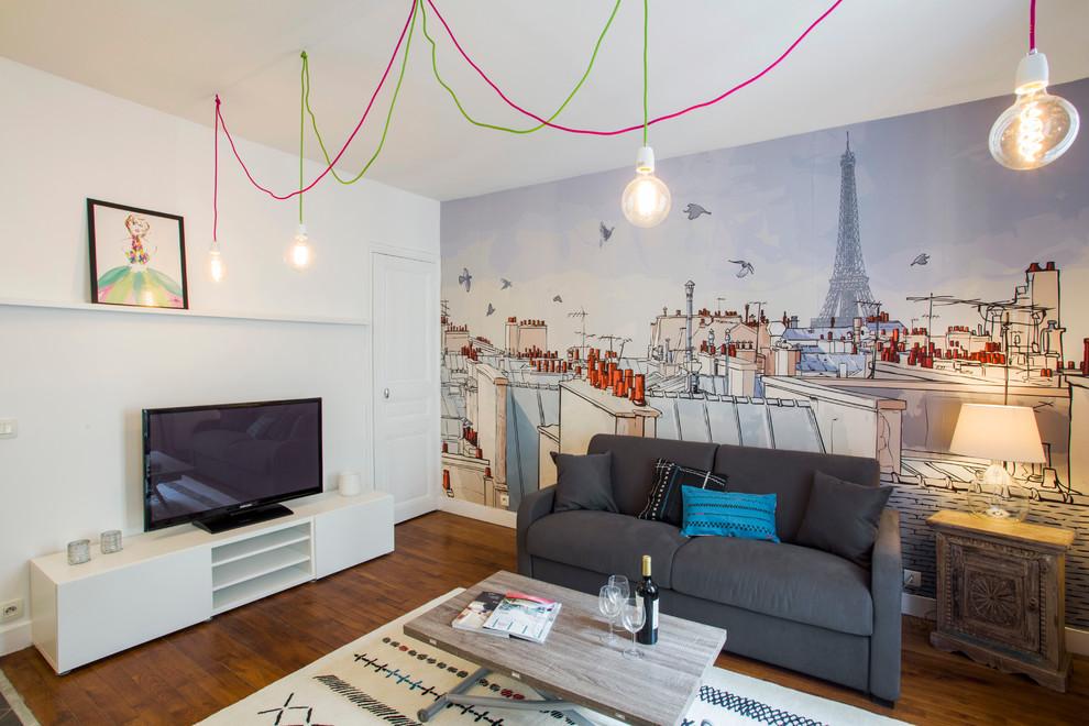 Cette photo montre une salle de séjour tendance de taille moyenne et fermée avec un mur blanc, un sol en bois brun, aucune cheminée et un téléviseur indépendant.
