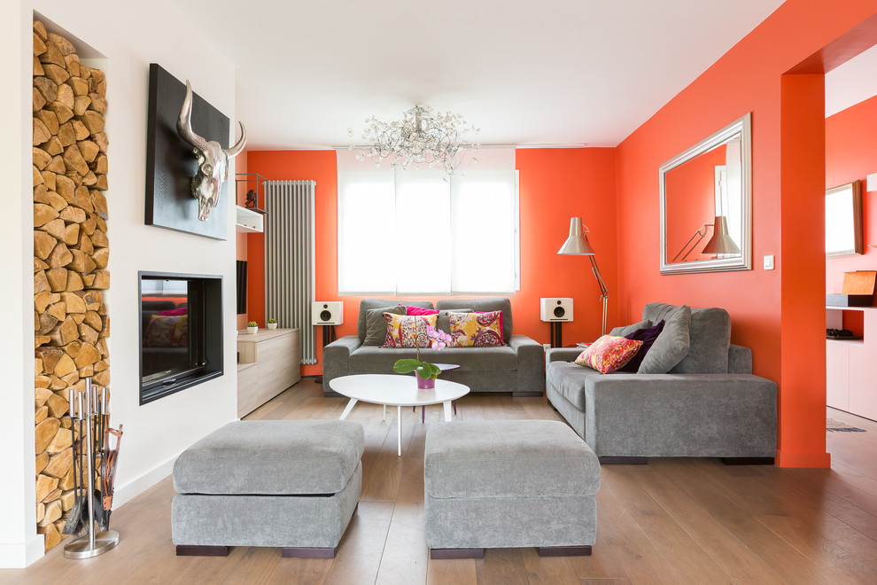 Large trendy open concept medium tone wood floor family room photo in Paris with orange walls, a standard fireplace and a wall-mounted tv
