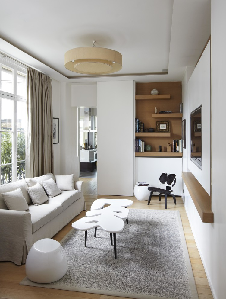 Example of a mid-sized danish open concept light wood floor family room design in Paris with white walls, no fireplace and a wall-mounted tv