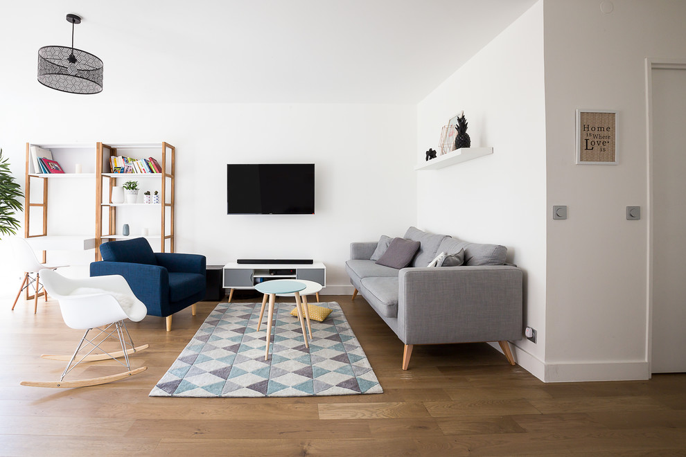Example of a mid-sized danish open concept medium tone wood floor family room library design in Paris with white walls, no fireplace and a wall-mounted tv