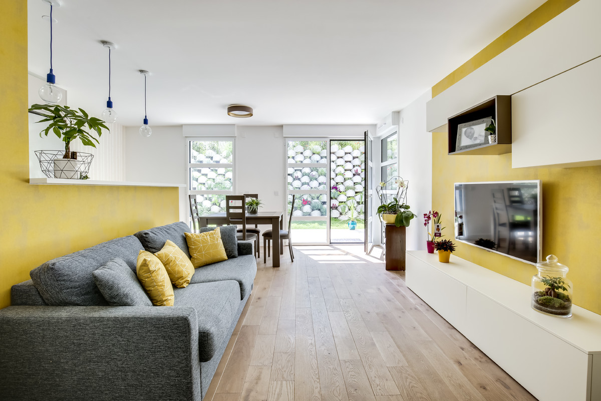 Example of a mid-sized trendy open concept light wood floor and brown floor family room design in Paris with yellow walls, a wall-mounted tv and no fireplace