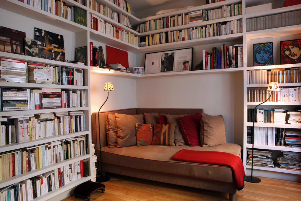 Example of a mid-sized trendy medium tone wood floor family room library design in Paris with white walls