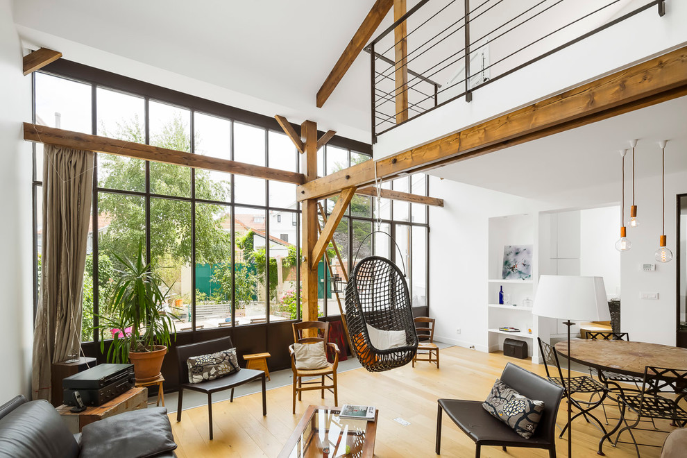 Mid-sized urban open concept light wood floor family room photo in Paris with white walls, no fireplace and no tv