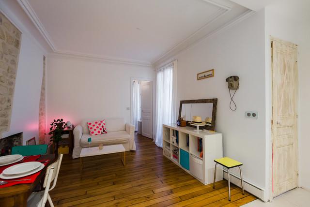Idée de décoration pour une salle de séjour nordique ouverte avec un mur blanc, un sol en bois brun, un poêle à bois et un manteau de cheminée en brique.