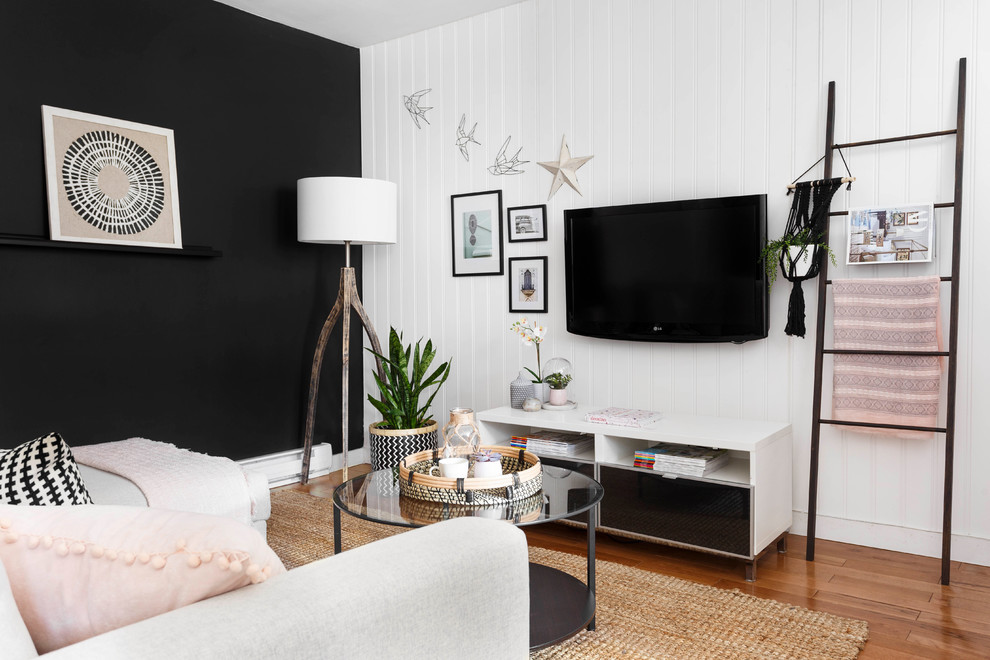 Family room - small scandinavian medium tone wood floor family room idea in Montreal with black walls, a wall-mounted tv and no fireplace