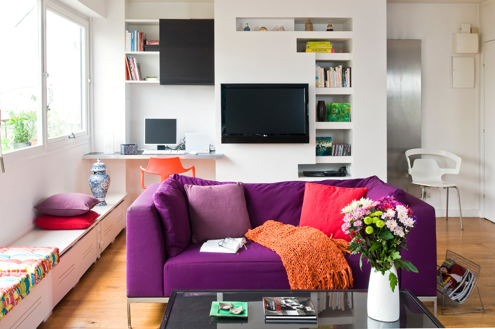 Inspiration for a mid-sized eclectic open concept medium tone wood floor family room remodel in Paris with white walls, no fireplace and a wall-mounted tv