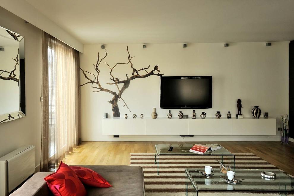 Imagen de sala de estar cerrada, actual, de tamaño medio, sin chimenea, con paredes blancas, suelo de madera clara y televisor colgado en la pared