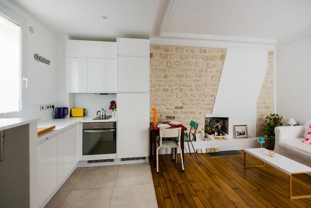 Idée de décoration pour une petite salle de séjour ouverte avec un sol en bois brun, un poêle à bois, un mur blanc et un manteau de cheminée en brique.