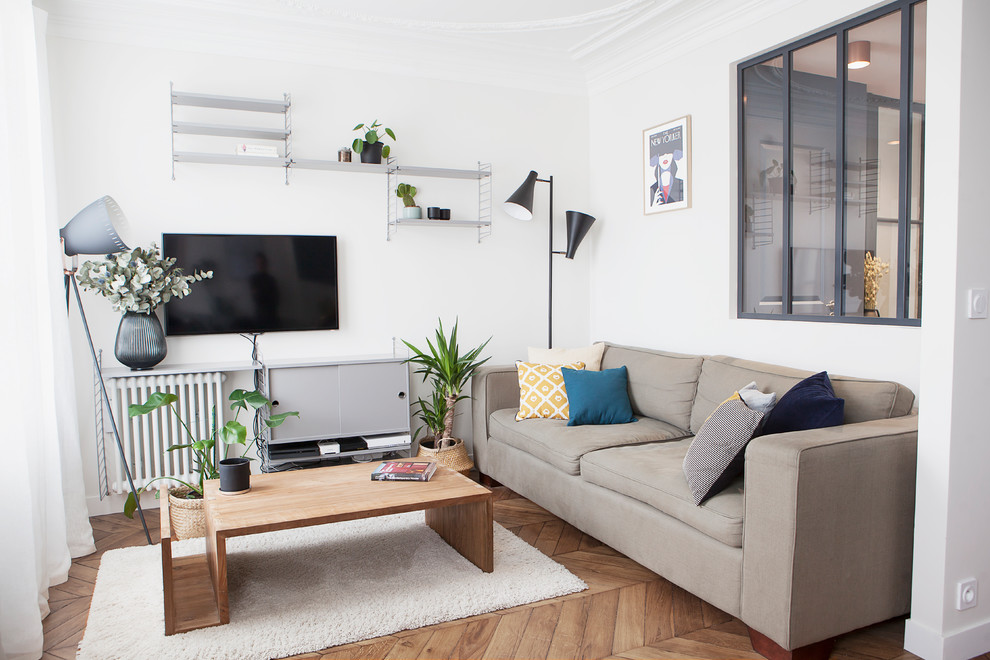 Small danish light wood floor and brown floor family room photo in Paris with a wall-mounted tv and white walls