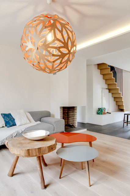 Inspiration for a mid-sized contemporary open concept light wood floor family room remodel in Paris with white walls, a corner fireplace and no tv