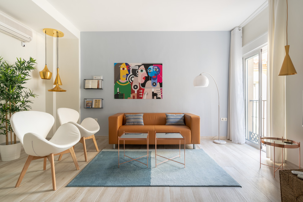 Example of a danish light wood floor and beige floor living room design in Malaga with white walls