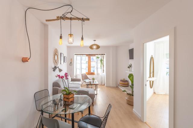 Modelo de salón abierto, mediterráneo, de tamaño medio, con paredes blancas, suelo de madera clara, chimenea tradicional, marco de chimenea de yeso y suelo marrón