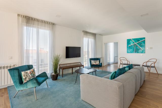 Ejemplo de salón para visitas abierto, moderno, grande, sin chimenea, con paredes blancas, suelo de madera en tonos medios y televisor colgado en la pared