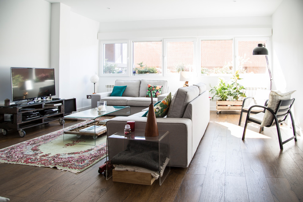 Example of a mid-sized danish formal and enclosed dark wood floor and brown floor living room design in Madrid with white walls, a tv stand and no fireplace