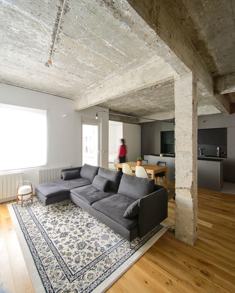 Living room - industrial open concept medium tone wood floor and brown floor living room idea in Bilbao with white walls