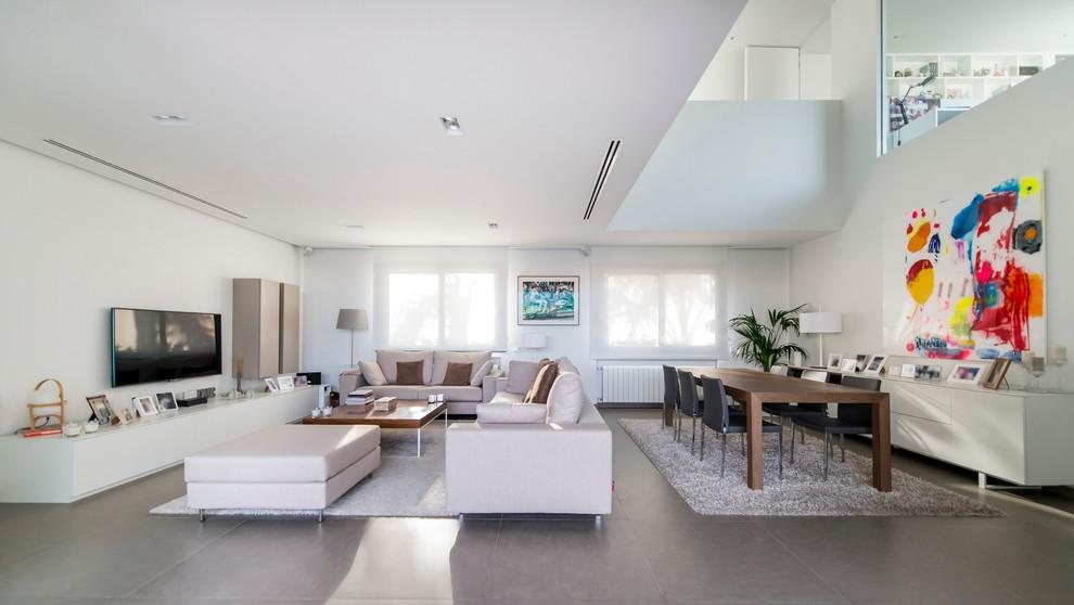 Modelo de salón abierto, minimalista, grande, sin chimenea, con paredes blancas, televisor colgado en la pared y suelo de baldosas de cerámica