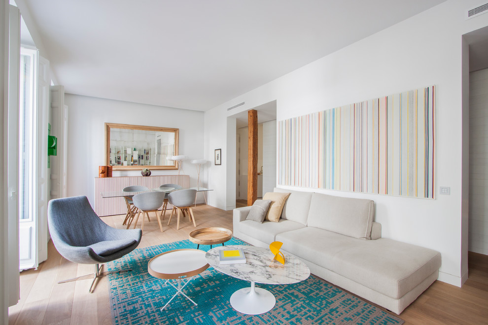 Example of a mid-sized danish open concept and formal medium tone wood floor living room design in Madrid with white walls, no fireplace and no tv