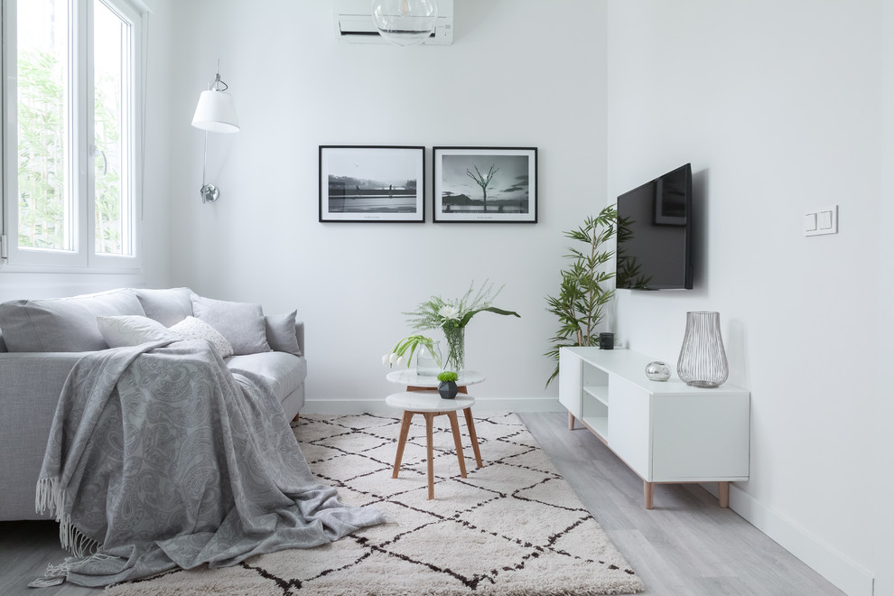 Small danish open concept gray floor and laminate floor living room photo in Madrid with white walls, no fireplace and a wall-mounted tv