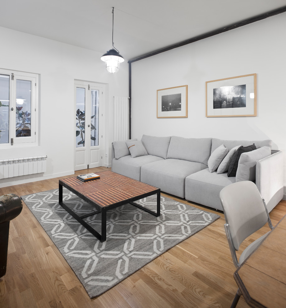 Example of an urban open concept and formal medium tone wood floor and beige floor living room design in Other with white walls