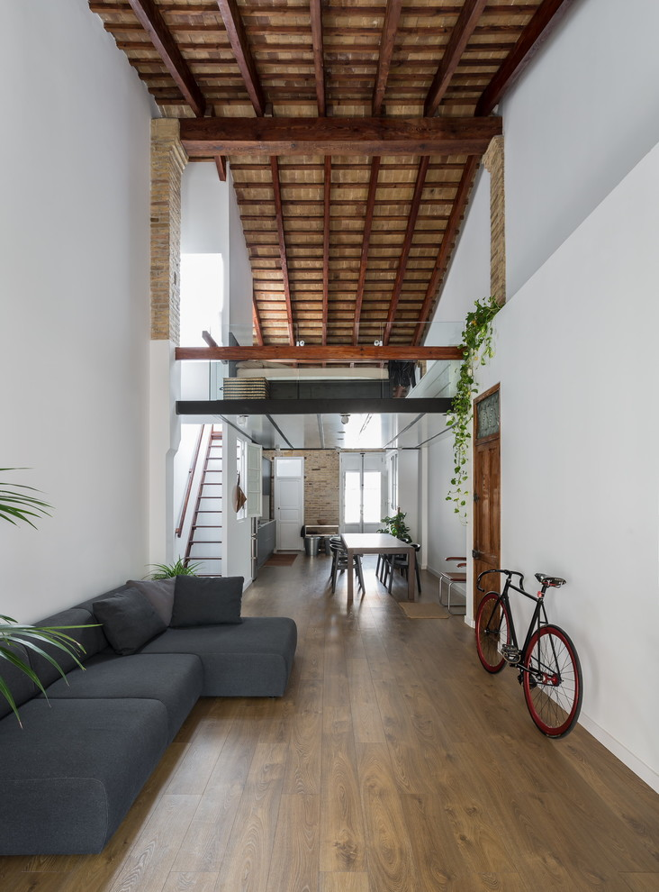 Inspiration for a mid-sized industrial formal and open concept medium tone wood floor living room remodel in Valencia with white walls, no fireplace and no tv