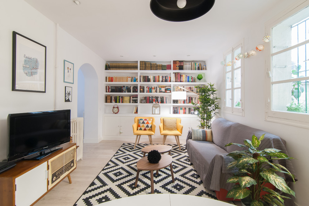 Living room library - mid-sized scandinavian open concept light wood floor and beige floor living room library idea in Madrid with white walls, no fireplace and a media wall