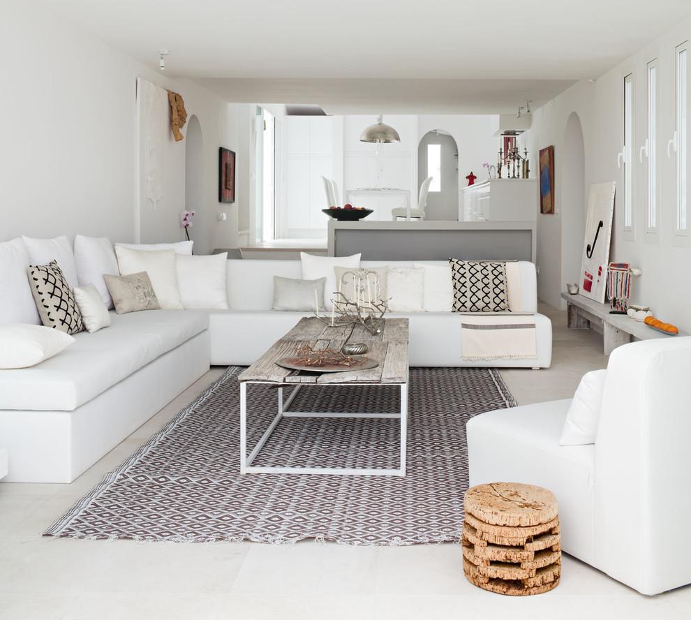 Imagen de salón para visitas abierto, mediterráneo, grande, sin chimenea y televisor, con paredes blancas y suelo de travertino