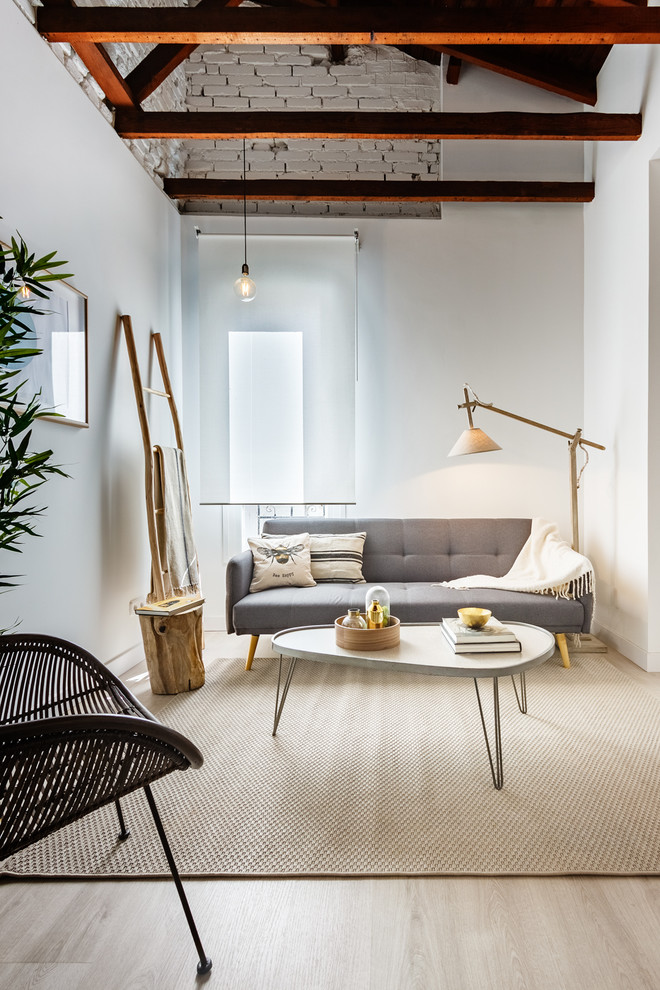 Example of a small danish light wood floor and beige floor living room design in Madrid with white walls, no fireplace and no tv