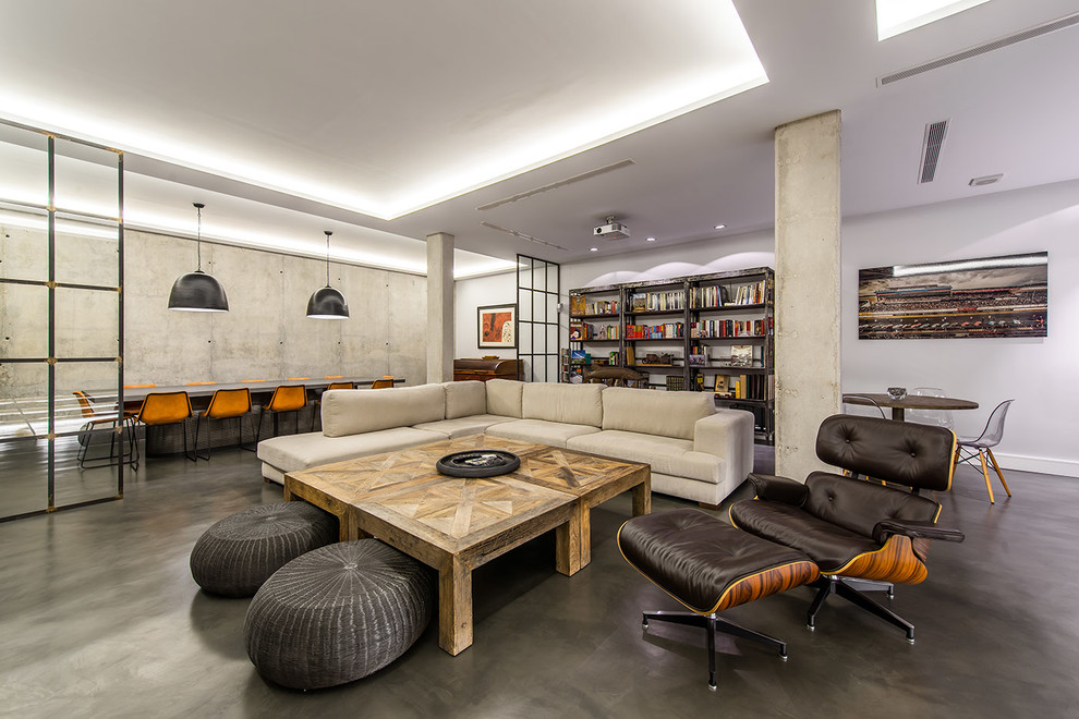 Example of a large urban open concept concrete floor living room library design in Madrid with no fireplace, a media wall and gray walls