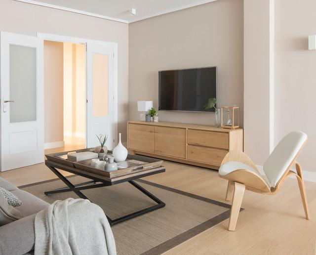 Diseño de salón para visitas cerrado, escandinavo, de tamaño medio, sin chimenea, con paredes beige, suelo de madera clara y televisor colgado en la pared