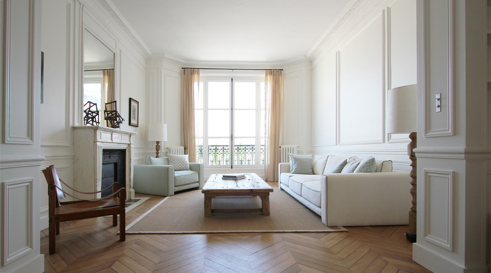 Large elegant formal and enclosed medium tone wood floor living room photo in Paris with white walls, a standard fireplace, a stone fireplace and no tv