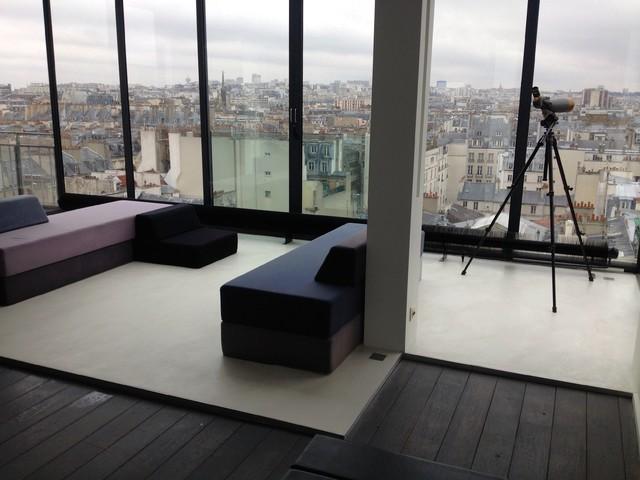 Inspiration pour un grand salon design avec béton au sol.