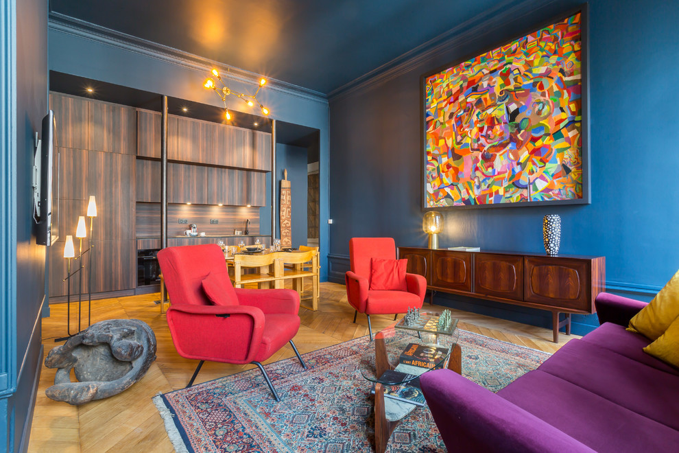 Example of an eclectic open concept medium tone wood floor and brown floor living room design in Lyon with blue walls