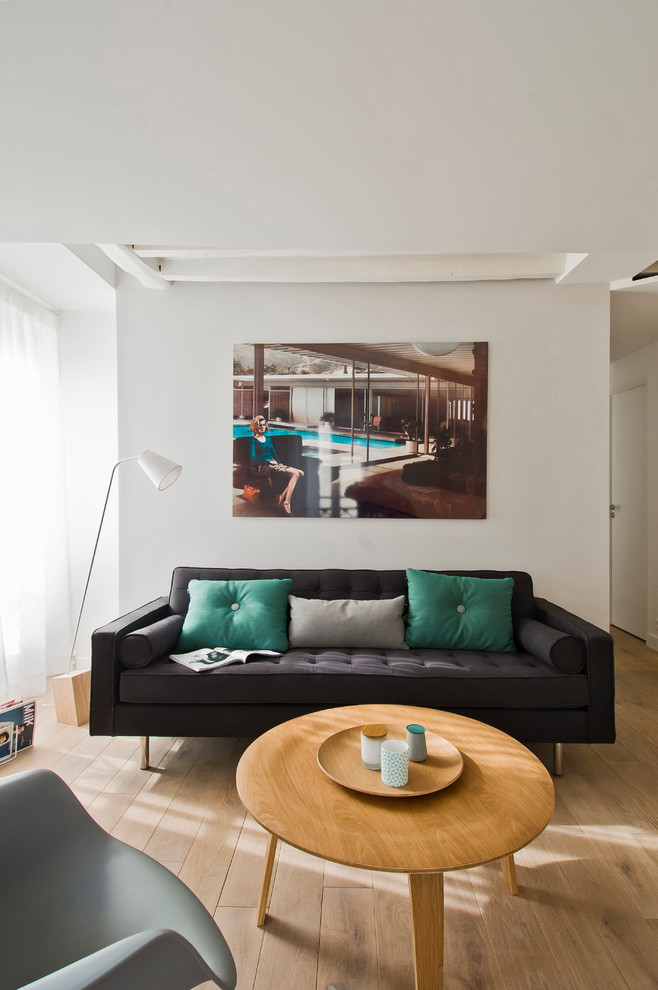 Example of a small danish open concept medium tone wood floor living room design in Paris with white walls