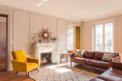 Canapé et cuir et fauteuil en velours jaune dans un salon vintage