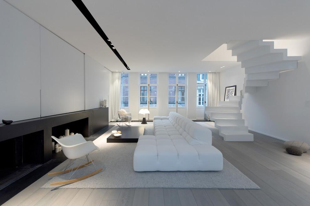 Foto på ett stort funkis allrum med öppen planlösning, med vita väggar, ett finrum och ljust trägolv