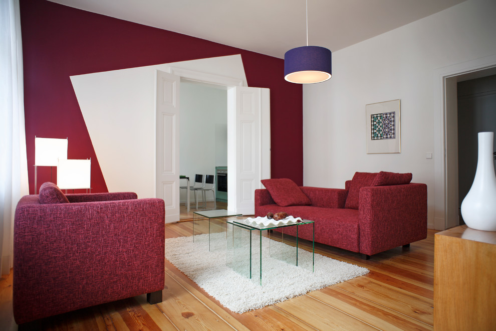 Living room - mid-sized contemporary formal and enclosed medium tone wood floor living room idea in Berlin with red walls