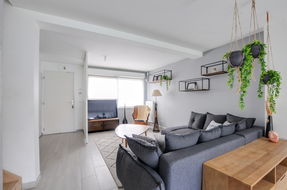 Example of a danish open concept ceramic tile and gray floor living room design in Strasbourg with gray walls, no fireplace and a tv stand