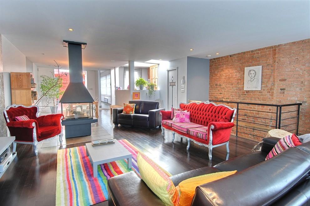 Aménagement d'un grand salon éclectique ouvert avec un sol en bois foncé et une cheminée double-face.