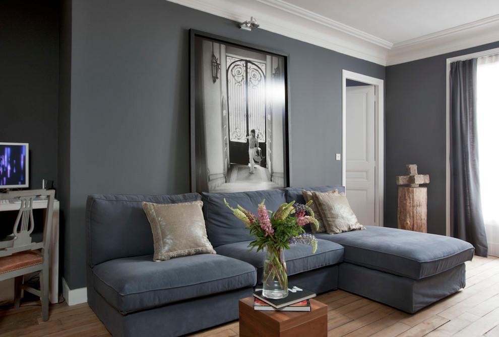 Idée de décoration pour un salon design de taille moyenne et fermé avec un mur gris, un sol en bois brun, aucune cheminée et aucun téléviseur.