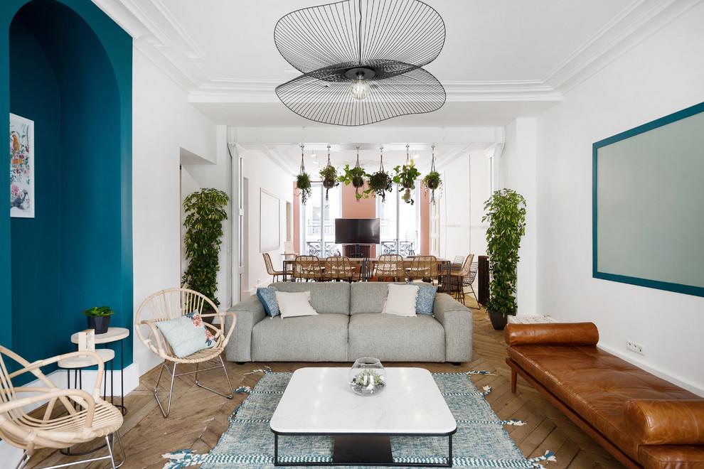 Danish open concept light wood floor and beige floor living room photo in Paris with blue walls