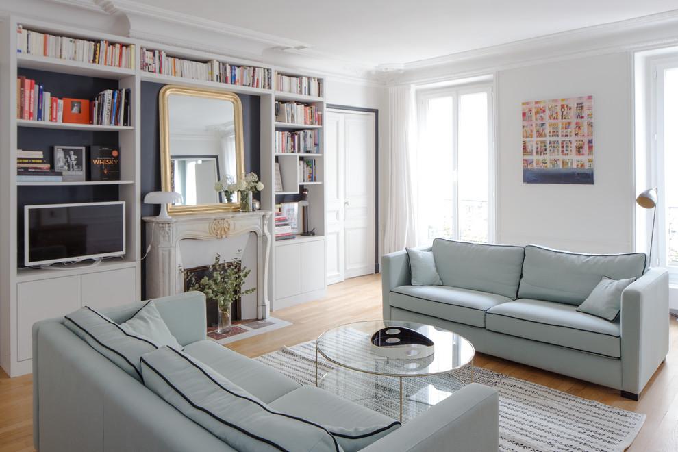Cette photo montre un salon chic fermé avec une salle de réception, un mur blanc, un sol en bois clair, une cheminée standard, un manteau de cheminée en pierre et un sol marron.