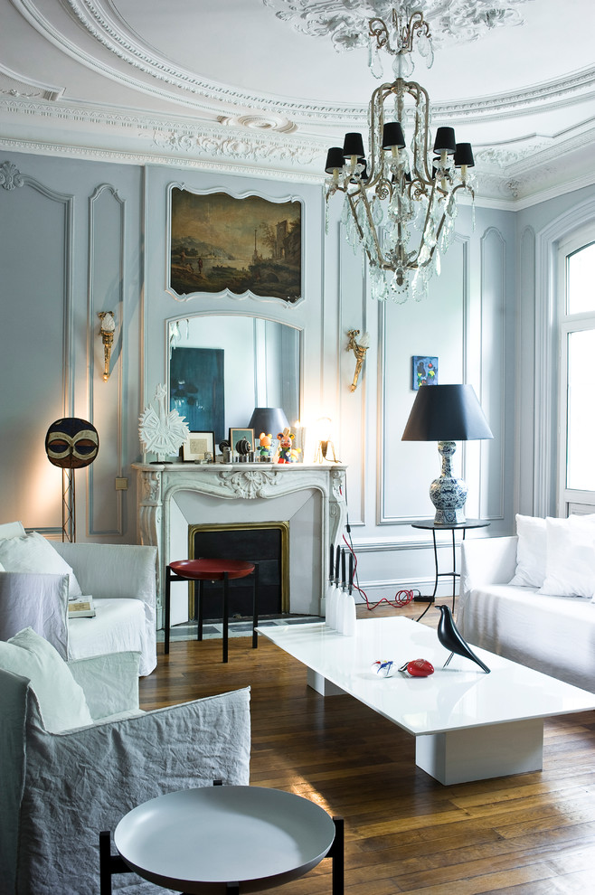 Living room - mid-sized eclectic formal and enclosed medium tone wood floor living room idea in Paris with a standard fireplace, white walls, a stone fireplace and no tv