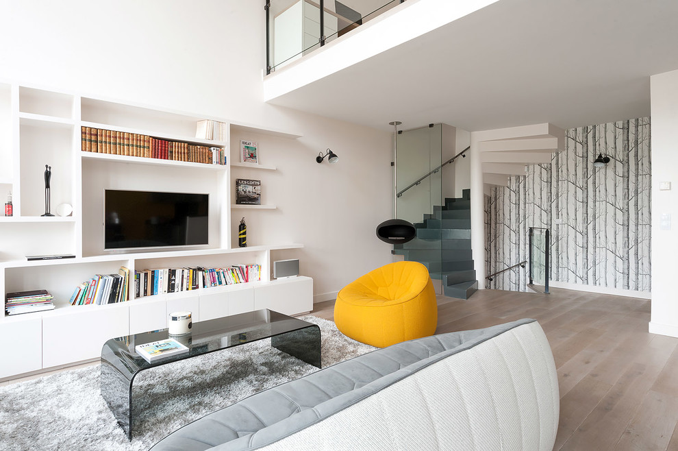 Inspiration for a mid-sized scandinavian open concept light wood floor living room library remodel in Paris with white walls and a media wall