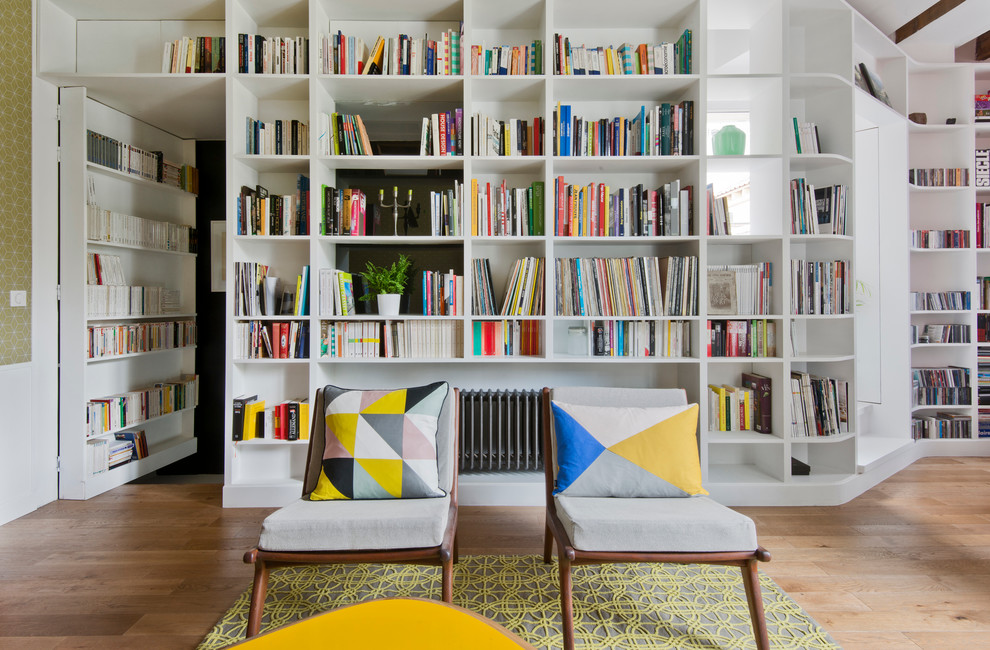 Example of a mid-sized danish enclosed light wood floor living room library design in Paris with white walls and no tv