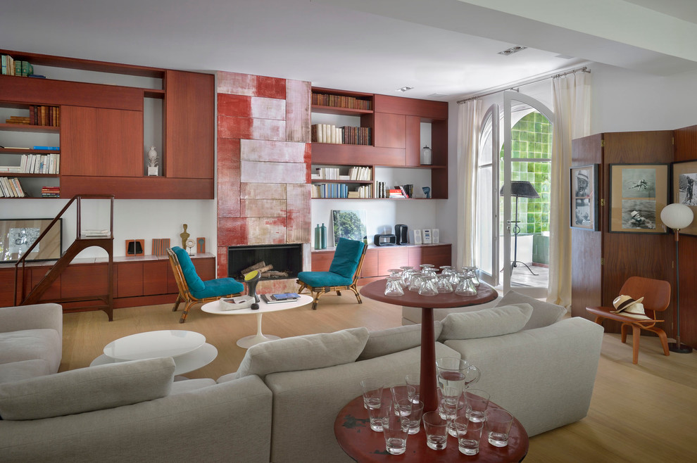 Example of a large tuscan open concept light wood floor living room library design in Paris with white walls, a standard fireplace and no tv