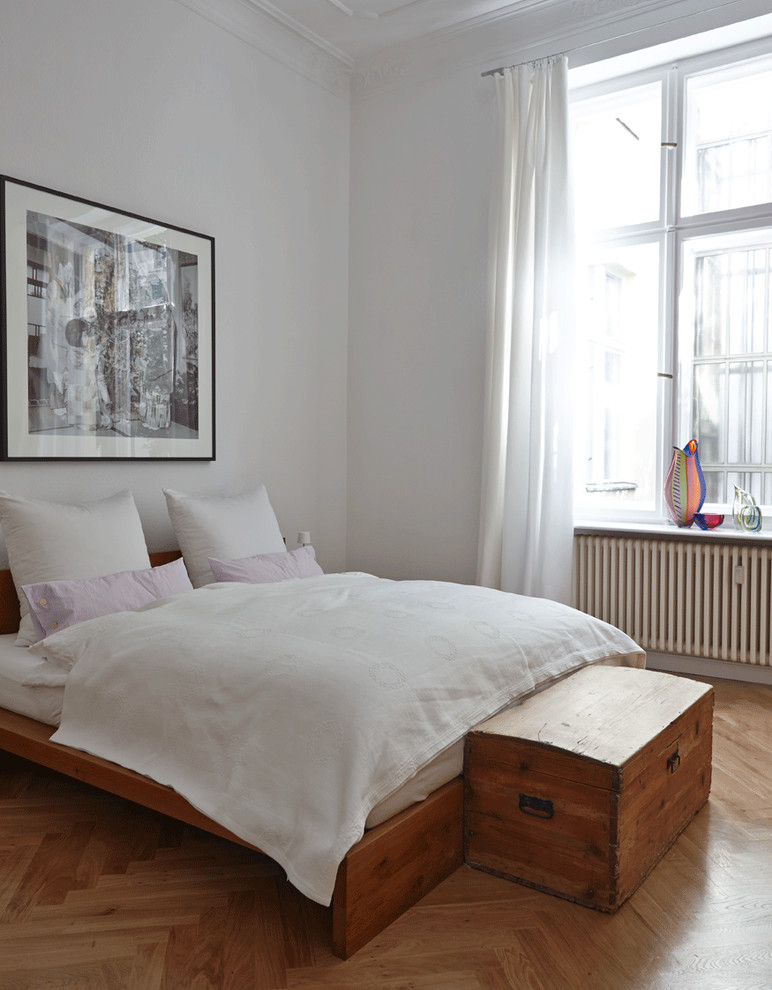 Example of a mid-sized trendy master light wood floor bedroom design in Berlin with white walls and no fireplace
